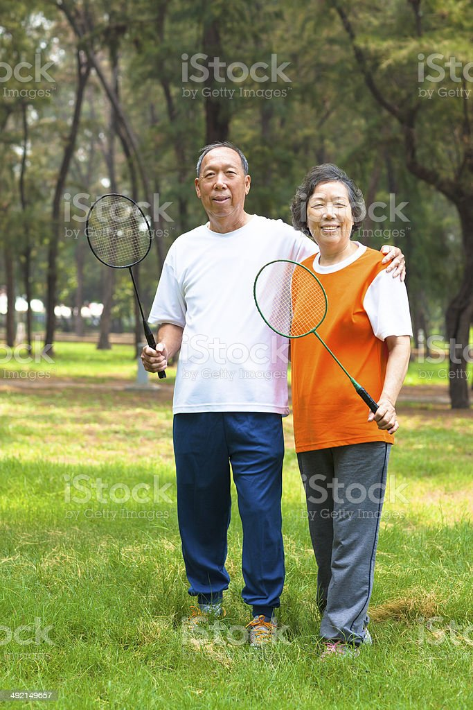 smiling older sibling and sister holding badminton racket stock photo