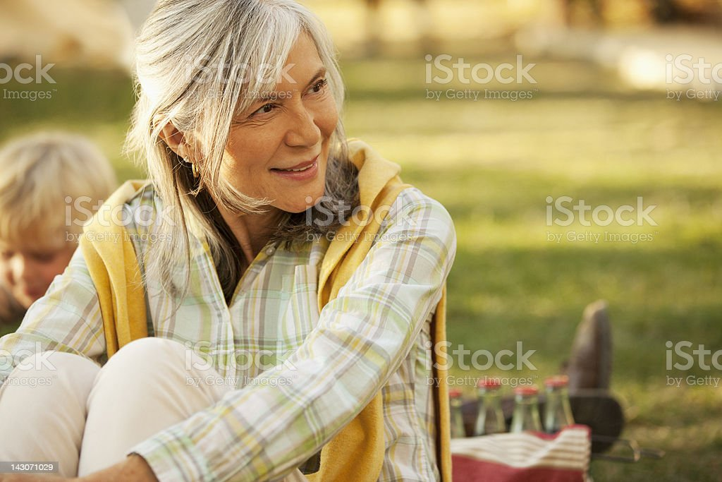 Smiling older woman relaxing outdoors stock photo