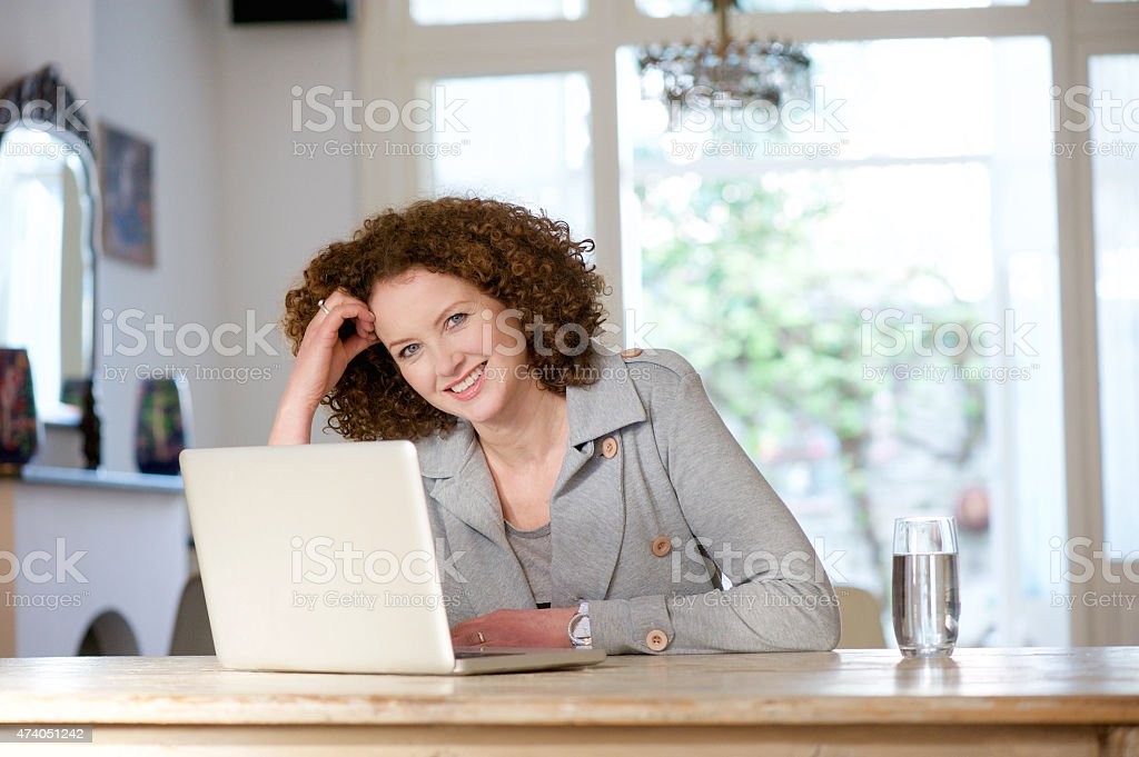 Smiling older woman sitting at table using laptop stock photo
