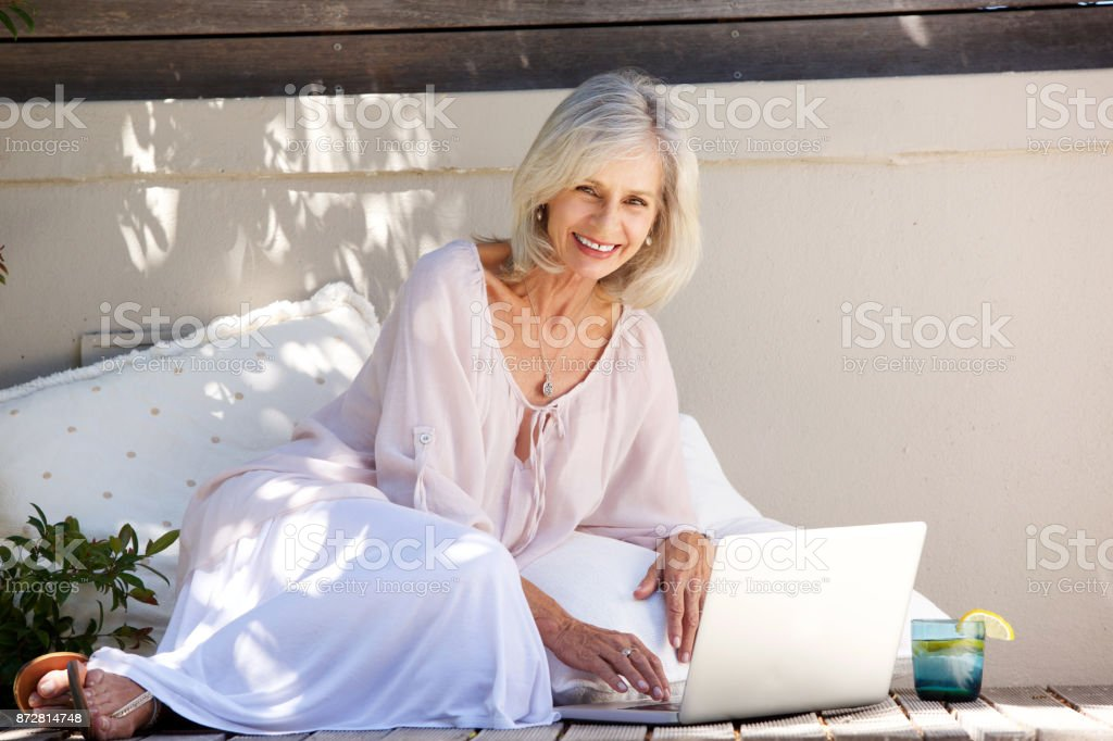 smiling older woman sitting outside with laptop stock photo
