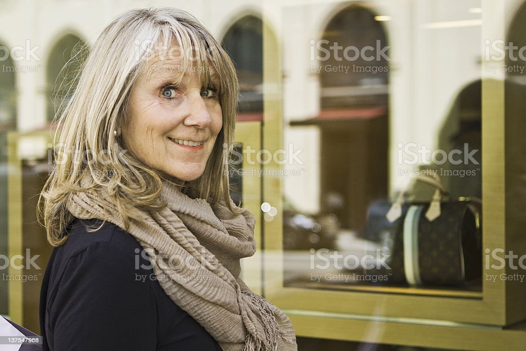 Smiling older woman window shopping stock photo