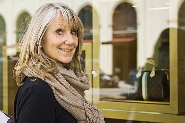 smiling older woman window shopping - vrouw 60 stockfoto's en -beelden