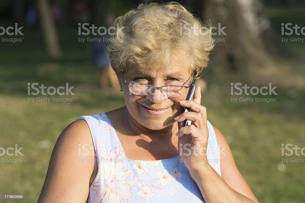 Smiling older woman with a phone. royalty-free stock photo
