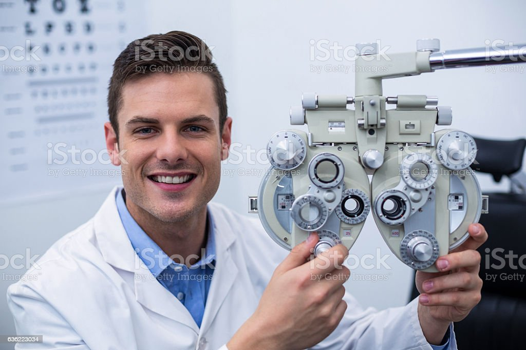 Smiling optometrist adjusting phoropter stock photo