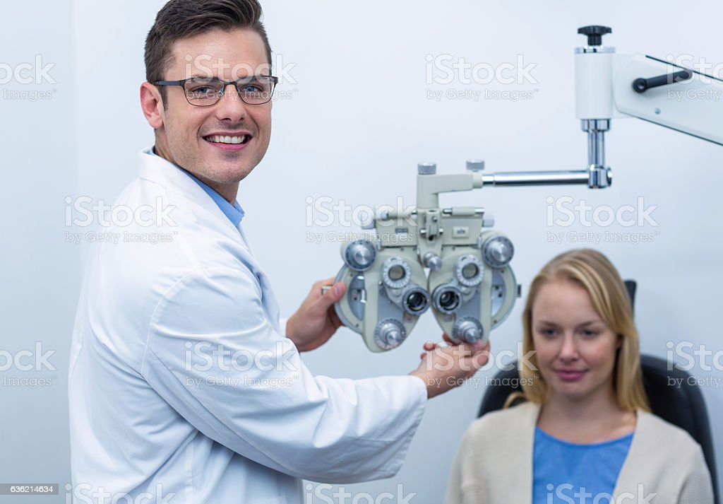 Smiling optometrist examining female patient on phoropter stock photo