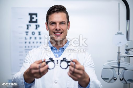 istock Smiling optometrist holding messbrille 636213978
