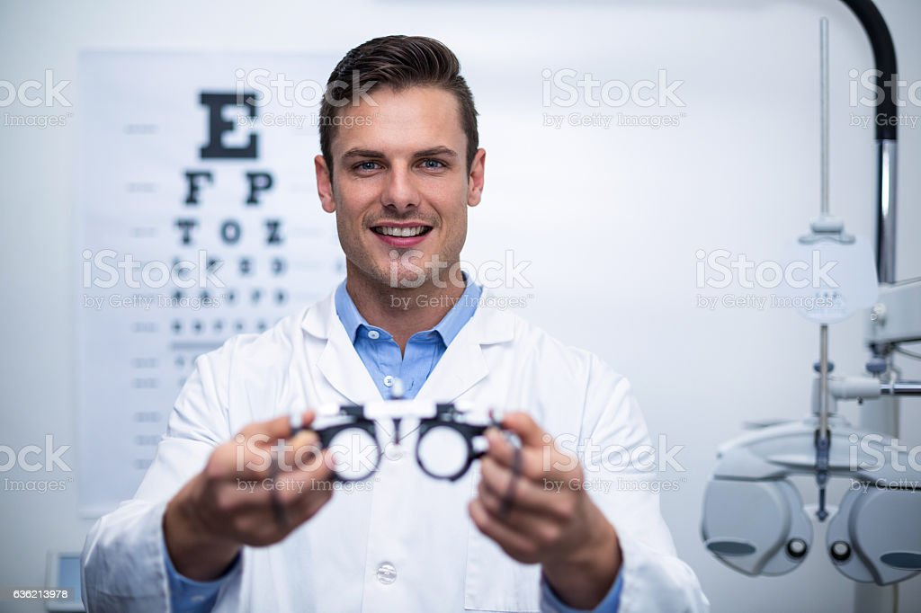 Smiling optometrist holding messbrille stock photo