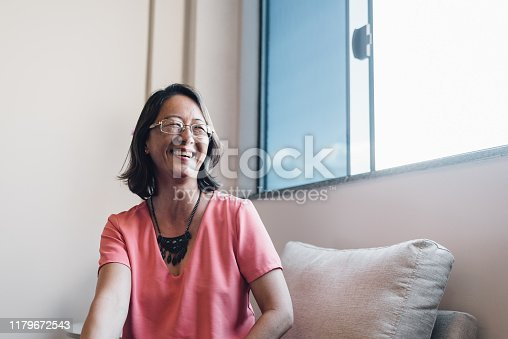 Smiling oriental mature woman at home