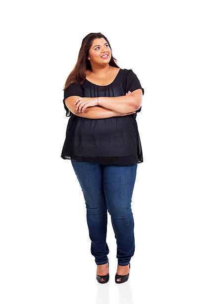 lächelnd übergewichtige frau nachschlagen - damen jeans übergrößen stock-fotos und bilder