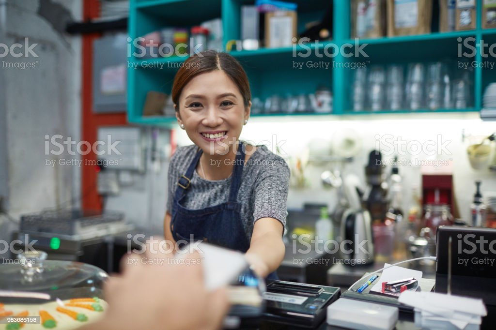 Smiling owner receiving payment at cafeteria stock photo