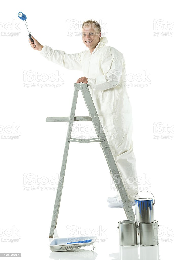Smiling painter painting with paint roller stock photo