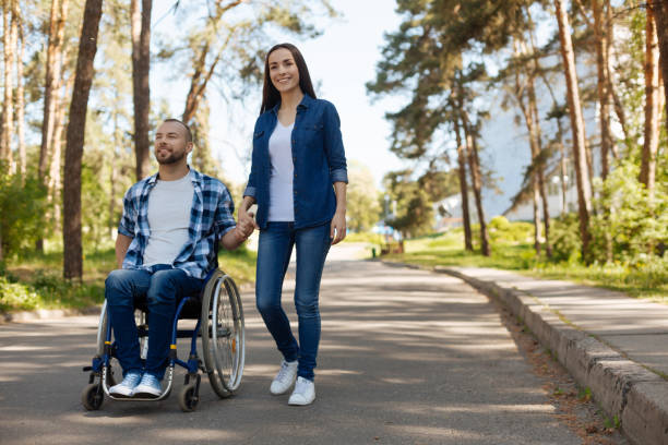 Smiling pair of lovers looking forward in one direction Breathing fresh air. Happy disabled male person sitting on his wheelchair looking forward while holding hands with his girlfriend paralysis stock pictures, royalty-free photos & images