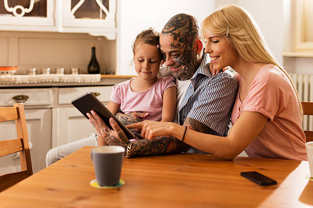 smiling parents surfing the internet with daughter on touchpad. - teaching stock photos and pictures