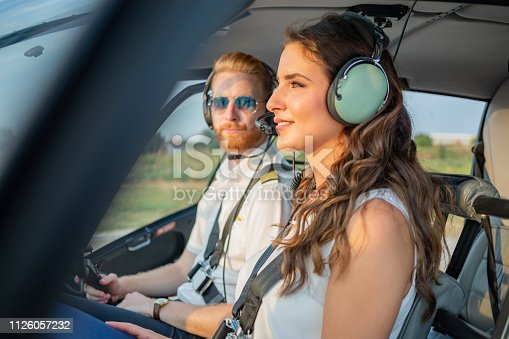Smiling female passenger sitting in helicopter cockpit with pilot with headphones on