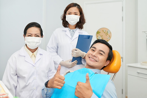 Smiling Patient And Doctors In Dental Office Stock Photo