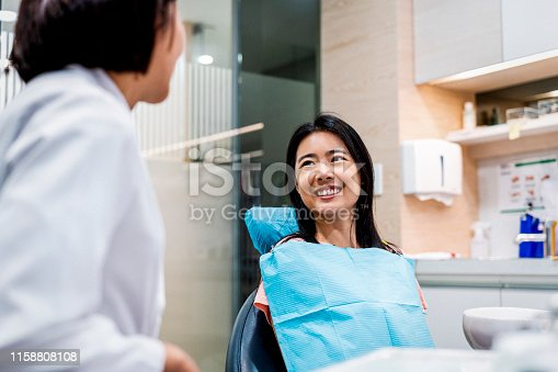 Smiling mid adult patient looking at healthcare worker. Female is sitting on dentist's chair. They are in dental clinic.