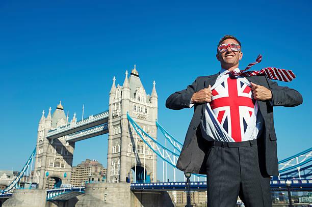 Smiling Patriotic British Businessman Superhero Union Jack Tower Bridge London stock photo