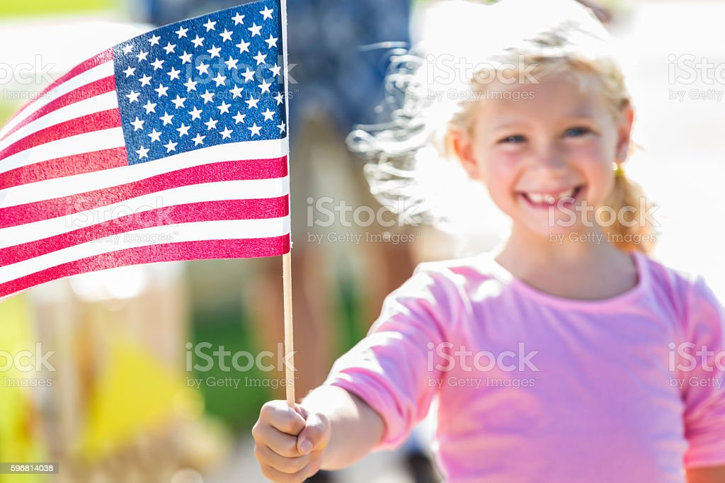 Smiling patriotic girl proudly holds American flag stock photo
