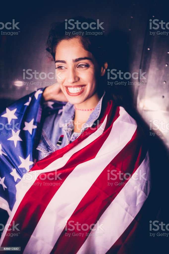 Smiling patriotic hipster girl with USA flag against urban background stock photo