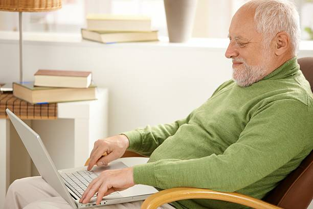 Smiling pensioner using laptop computer stock photo