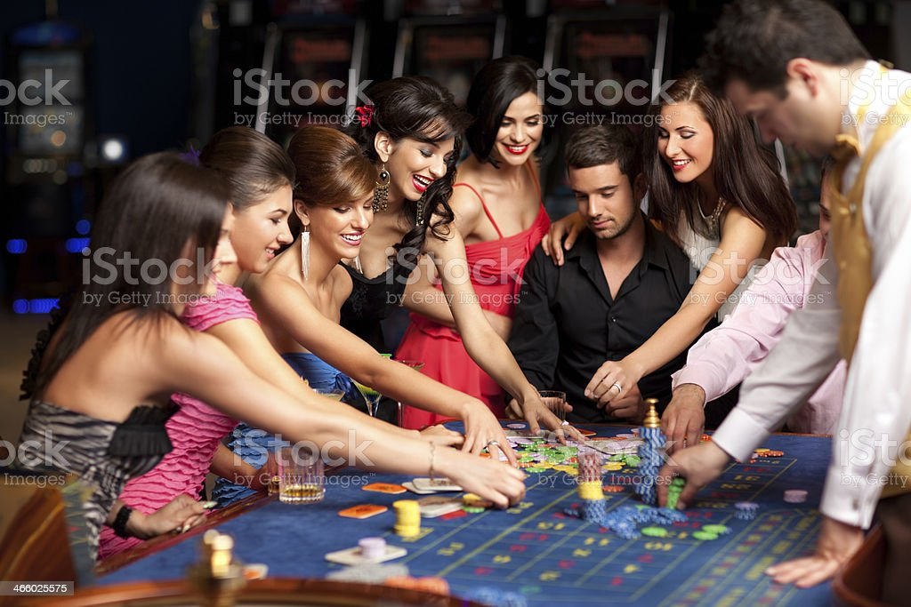 smiling people and dealer playing roulette royalty-free stock photo