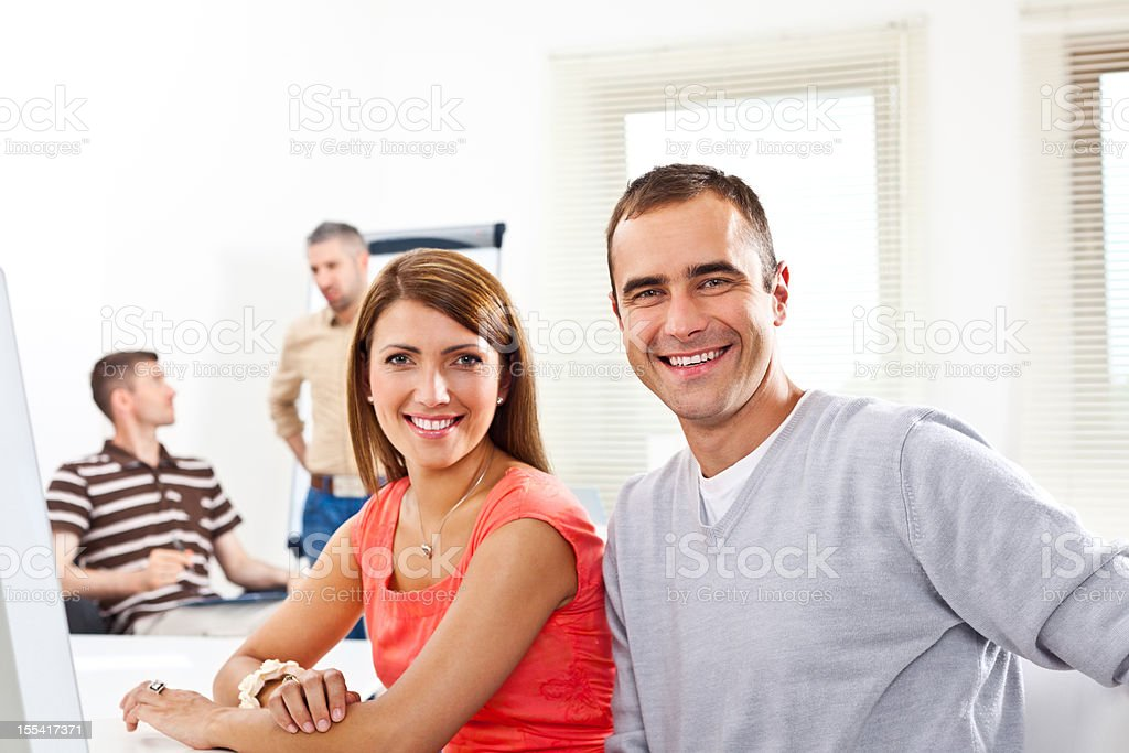 Smiling people at work Creative agency, four people working in two groups in an office. Focus on the couple smiling at the camera. Adult Stock Photo