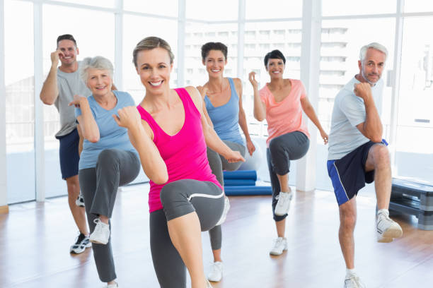 smiling people doing power fitness exercise at yoga class - aerobics stock photos and pictures