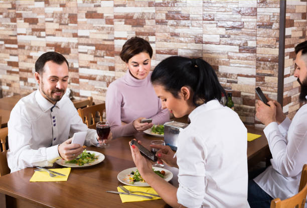 Smiling people having dinner and using smartphones Smiling people having dinner and using smartphones at restaurant table old man working in a pub stock pictures, royalty-free photos & images