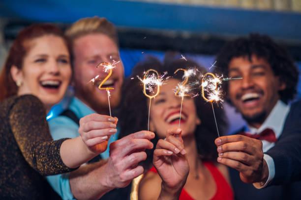 gente sonriente sosteniendo chispas - año nuevo fotografías e imágenes de stock