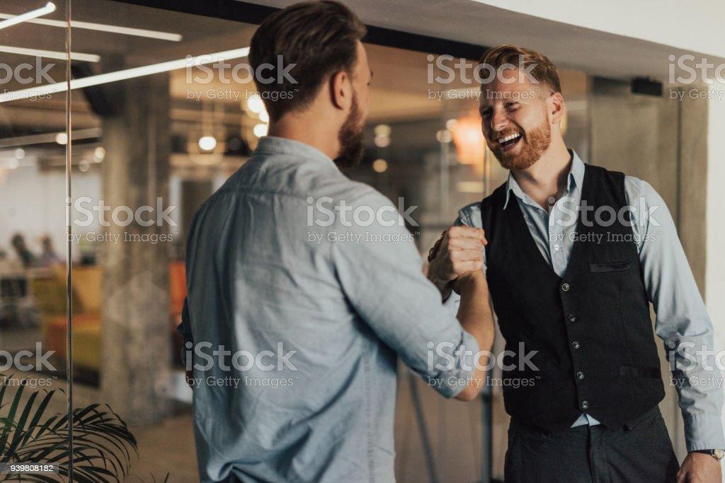Lächelnde Menschen in Business-Kleidung sind die Hände schütteln. – Foto