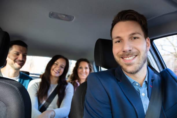 Personnes de sourire s'asseyant dans la voiture - Photo