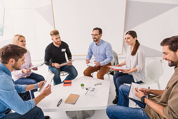 Smiling people sitting in circle Smile will save world. Cheerful visitors are in light room, sitting around table and speaking debate stock pictures, royalty-free photos & images
