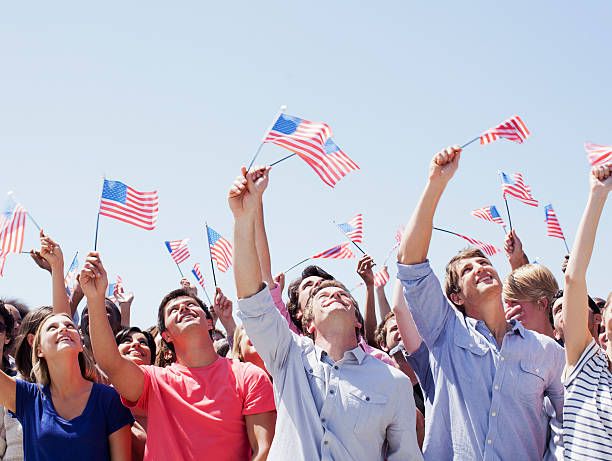 Smiling people waving American flags and looking up in crowd  citizenship stock pictures, royalty-free photos & images