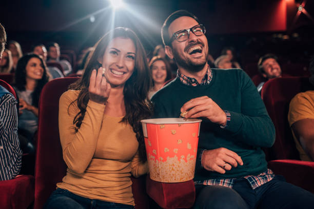 smiling people with popcorn in cinema - film festival stock photos and pictures
