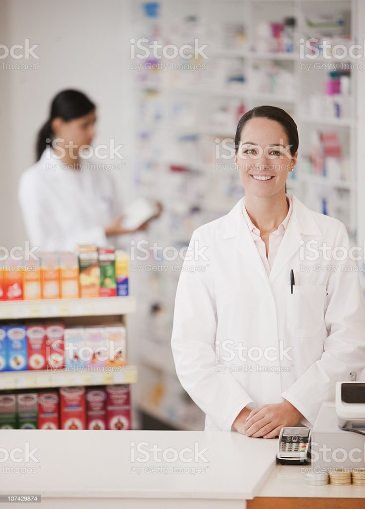 Smiling pharmacist in drug store standing at cash register royalty-free stock photo