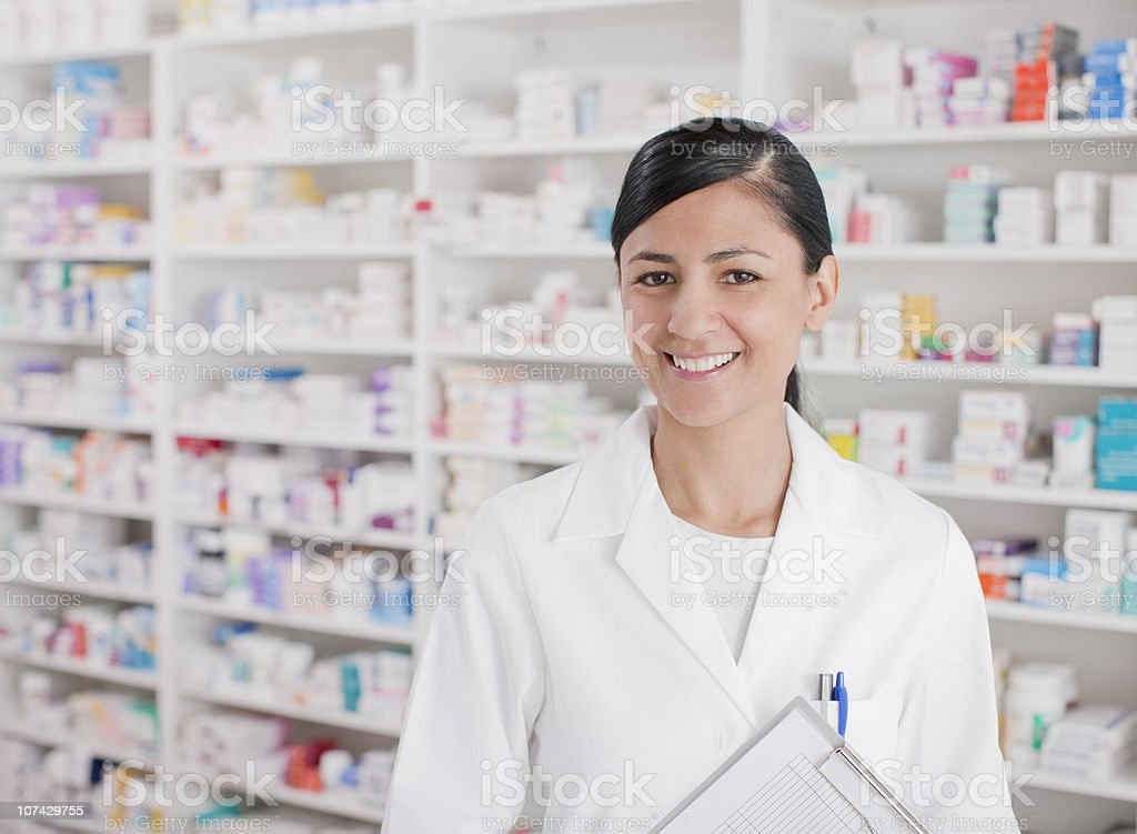 Smiling pharmacist standing in drug store stock photo