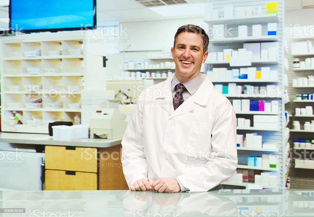 Smiling pharmacist standing pharmacy stock photo