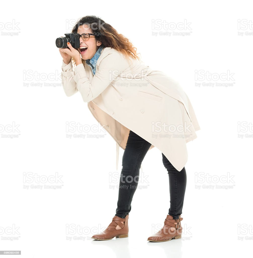 Smiling photographer in action with camera royalty-free stock photo