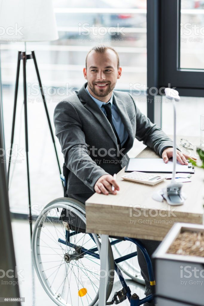 smiling physically handicapped businessman in suit on wheelchair working at office stock photo