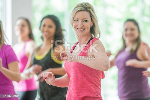 A multi-ethnic group of adult women are taking a dance fitness class indoors. They are wearing casual, colourful sports wear. They are posing and smiling at the camera.