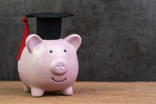istock Smiling pink piggy bank wearing graduated hat on wooden table with dark black background and copy space, education fund, Scholarships, university cost and expense or saving for student loan concept 1170398457