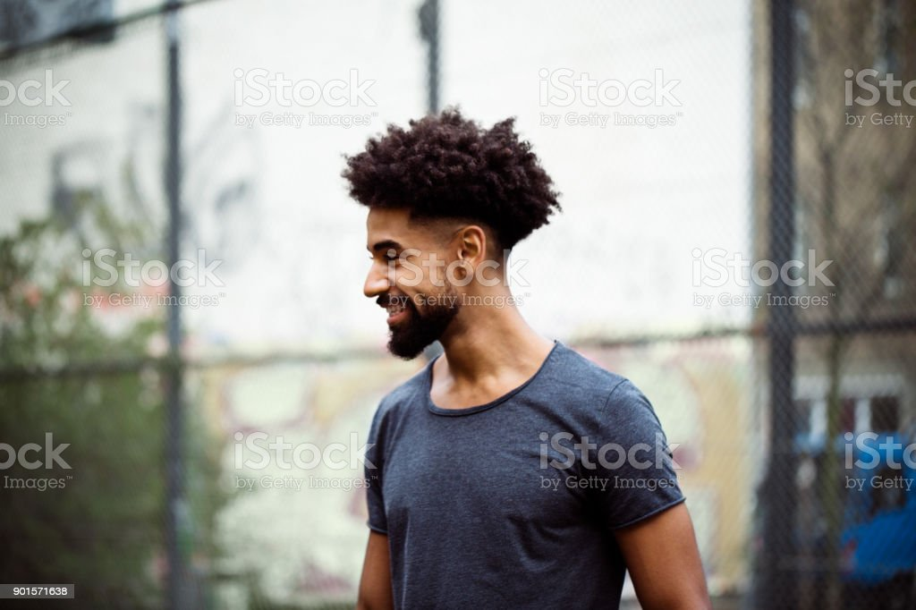 Smiling player with frizzy hair looking away stock photo