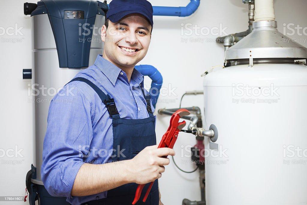 Smiling plumber at work stock photo