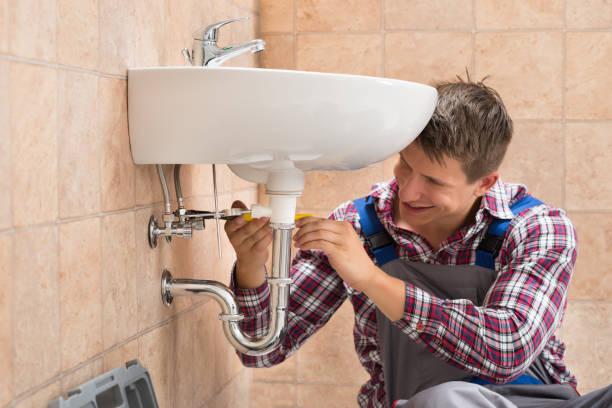 lächelnd klempner reparieren waschbecken - kanalisationsabflüsse stock-fotos und bilder