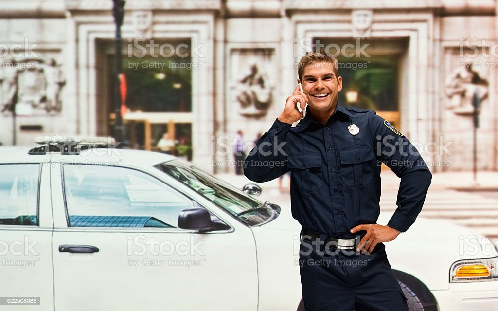 Smiling police on phone outdoors stock photo