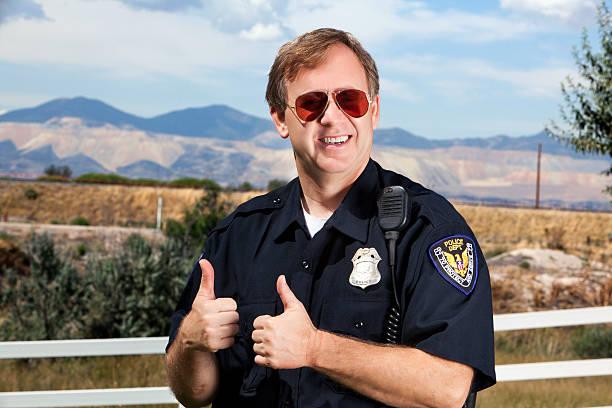 sonriendo policeman pulgares arriba con gafas de sol - feliz dia del policia fotografías e imágenes de stock