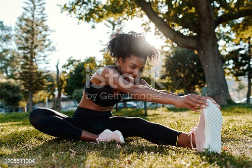 Smiling young woman doing exercise in the park stretching before doing a run
