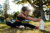 istock Smiling portrait of an sporty fit african american young woman sitting on lawn stretching her legs in the park - happy young black woman warming up her muslces before running 1205511004