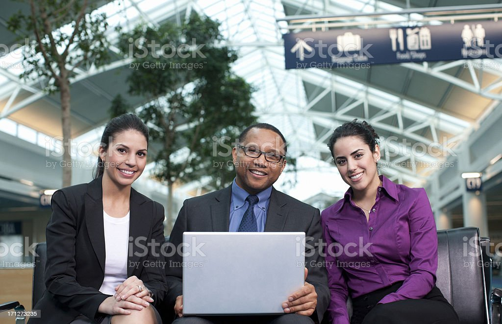 Smiling Portrait of Business Team at Airport with Laptop stock photo