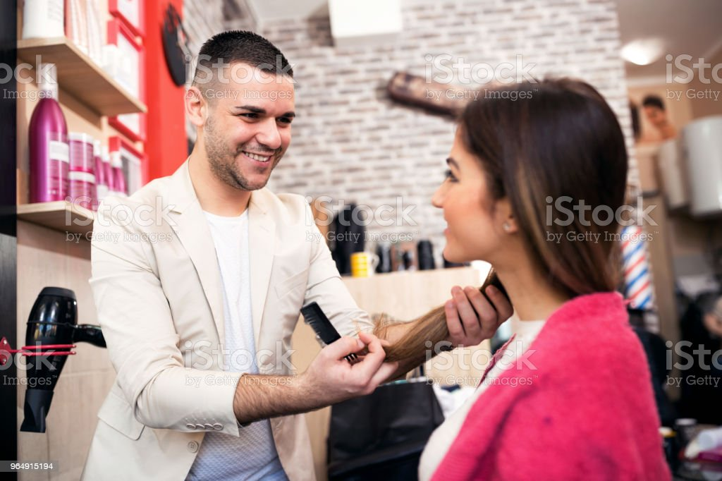 Smiling positive hair stylist talking with his client royalty-free stock photo